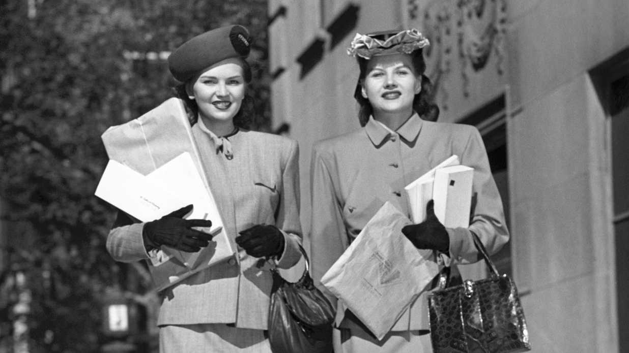 Two fashionable women walking carrying packages