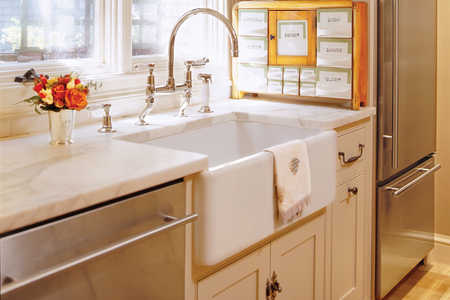 /in the remodeled kitchen, a white farmers sink with creamy marble countertops and a stainless steel refrigerator
