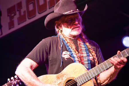 Willie Nelson playing guitar on stage at John T. Floore's Country Store