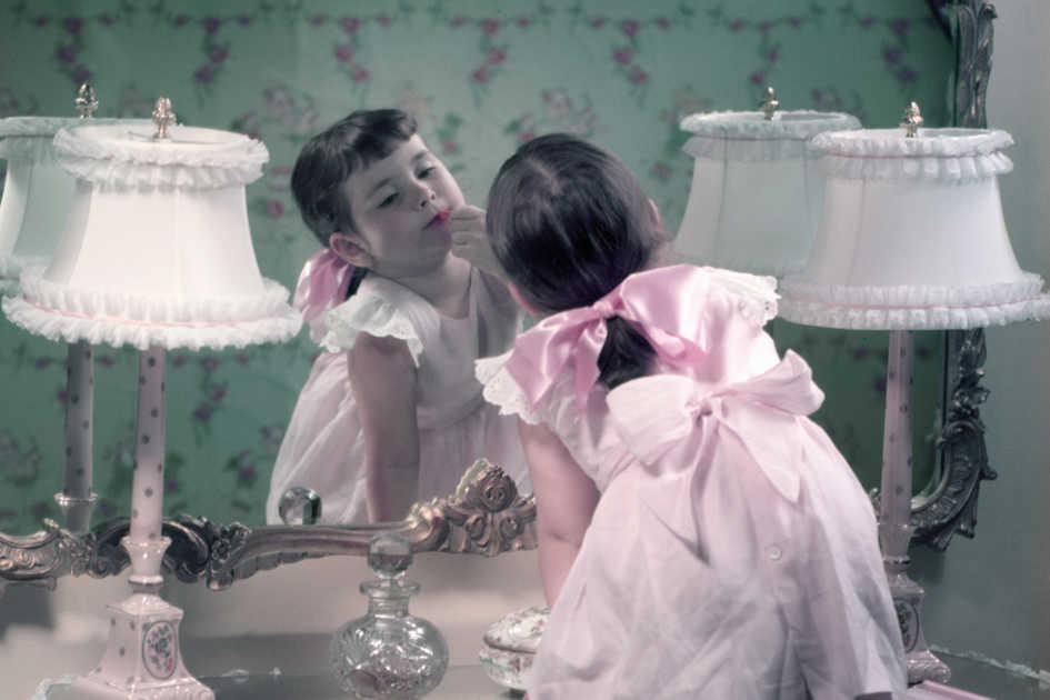 Girl with Bows Putting on Lipstick